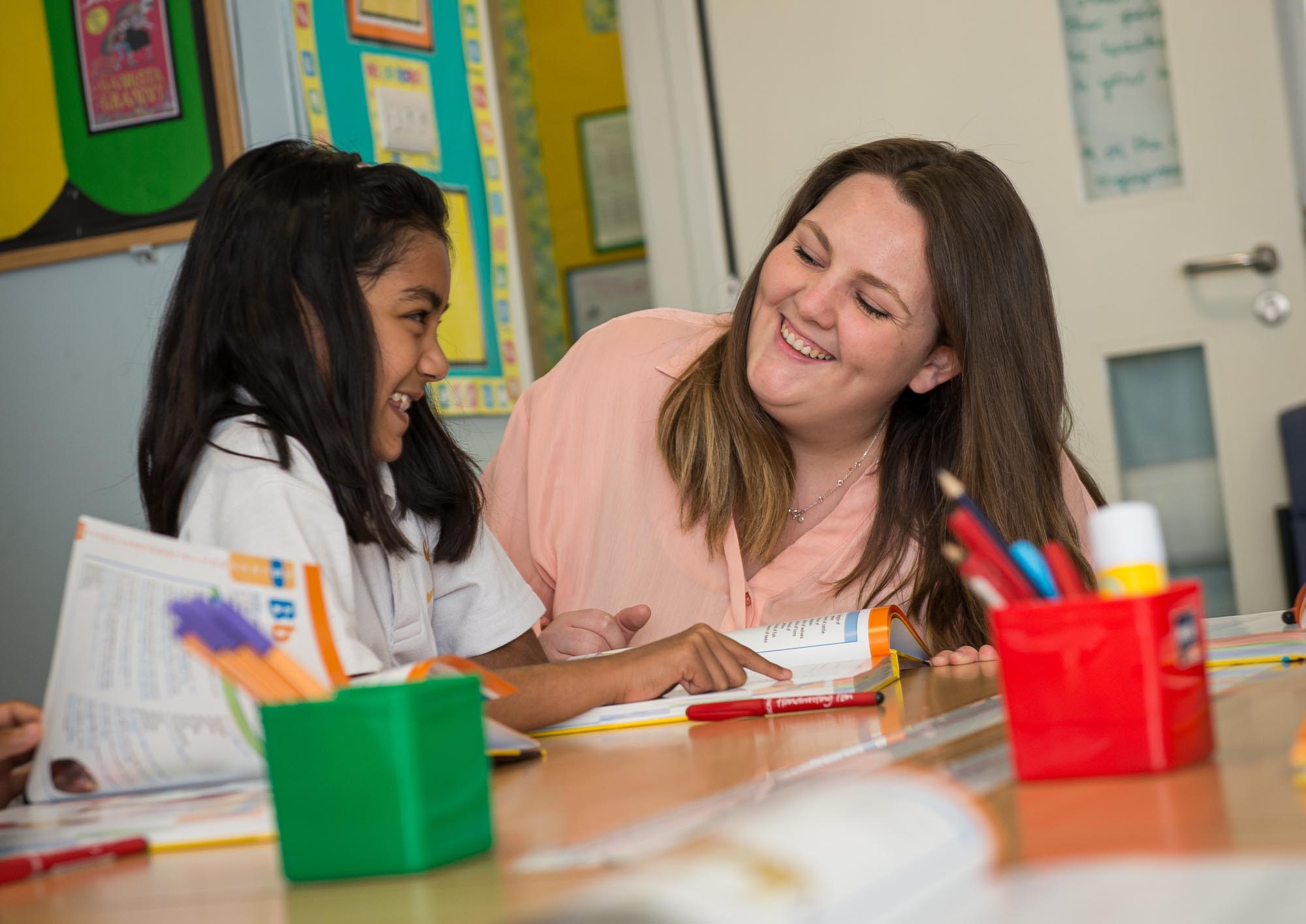 Teacher and pupil laughing