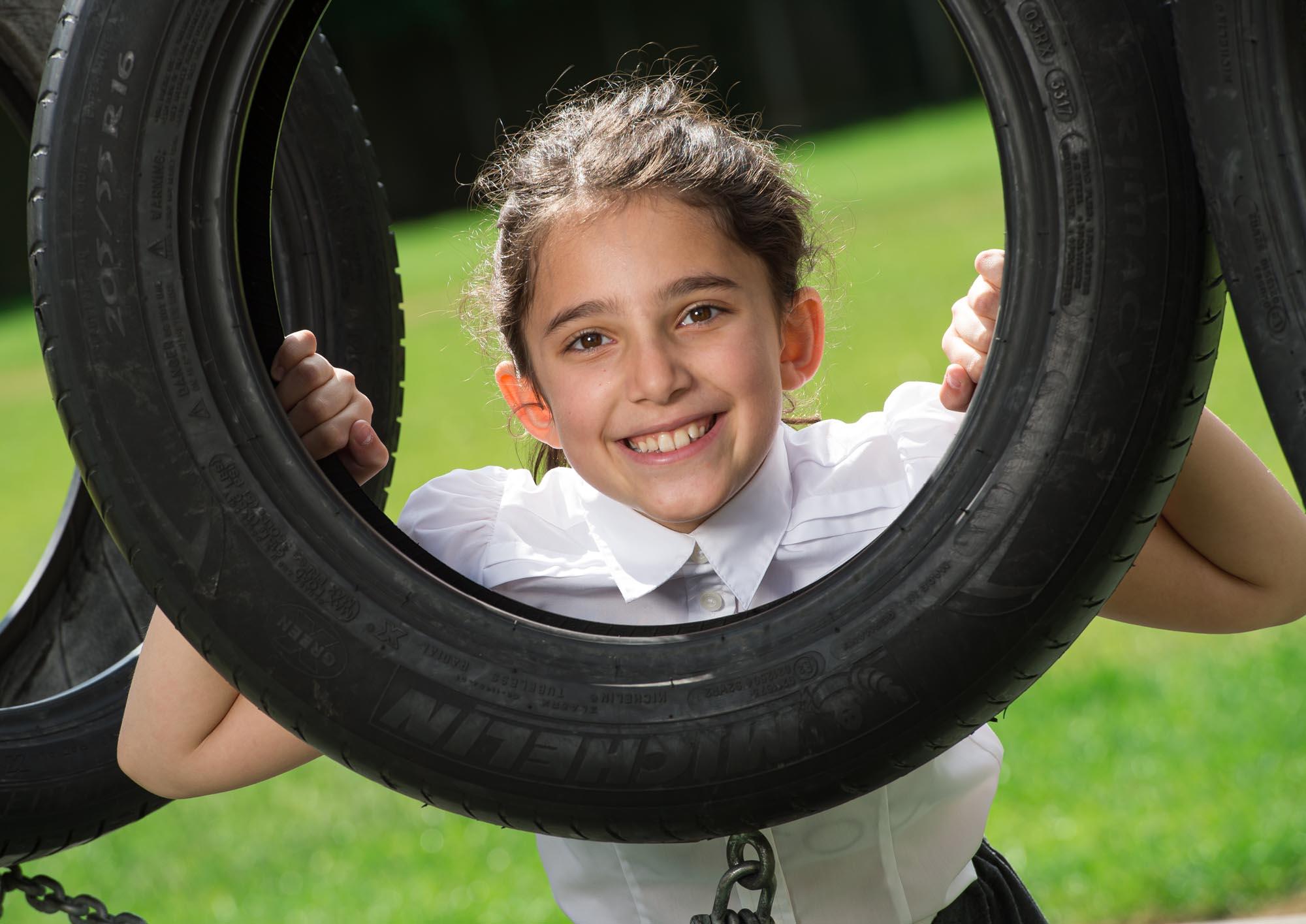 Girl looking through tyre