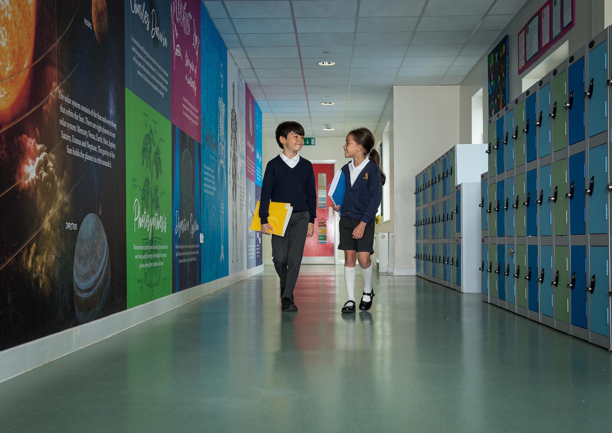 Boy and girl walking in science corridor