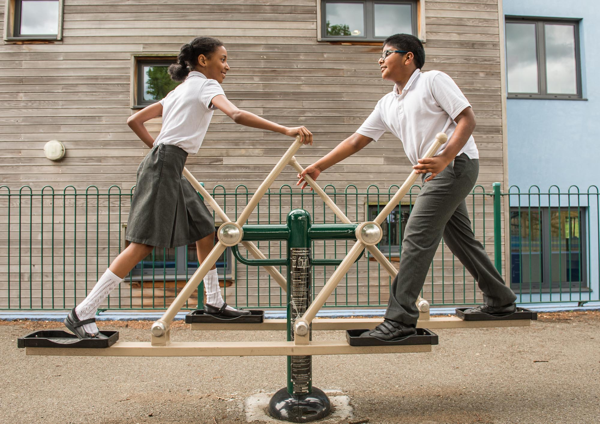 Boy and girl exercising on outdoor gym