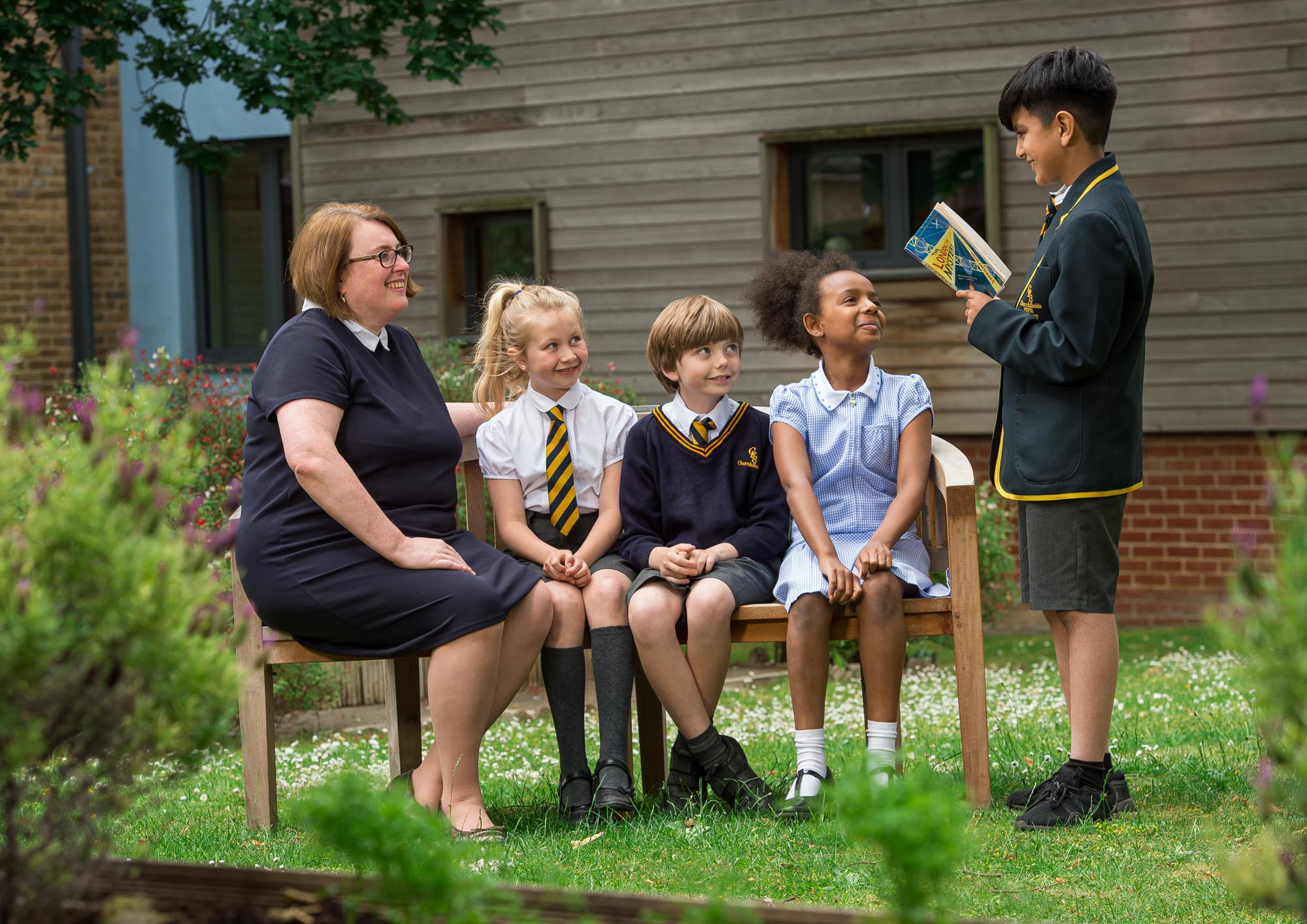 Head teacher and children on bench listening to boy reading book out load