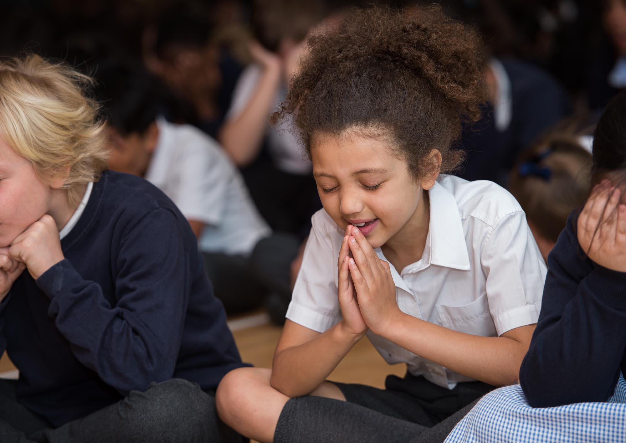 Girl praying in assembly