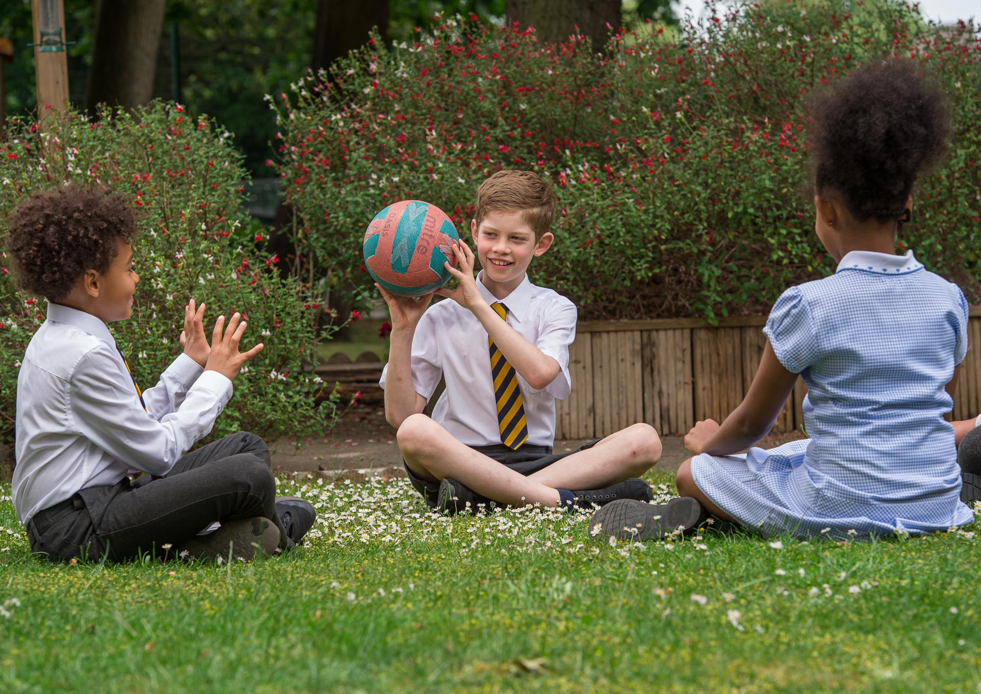 Three children playing ball in the grass