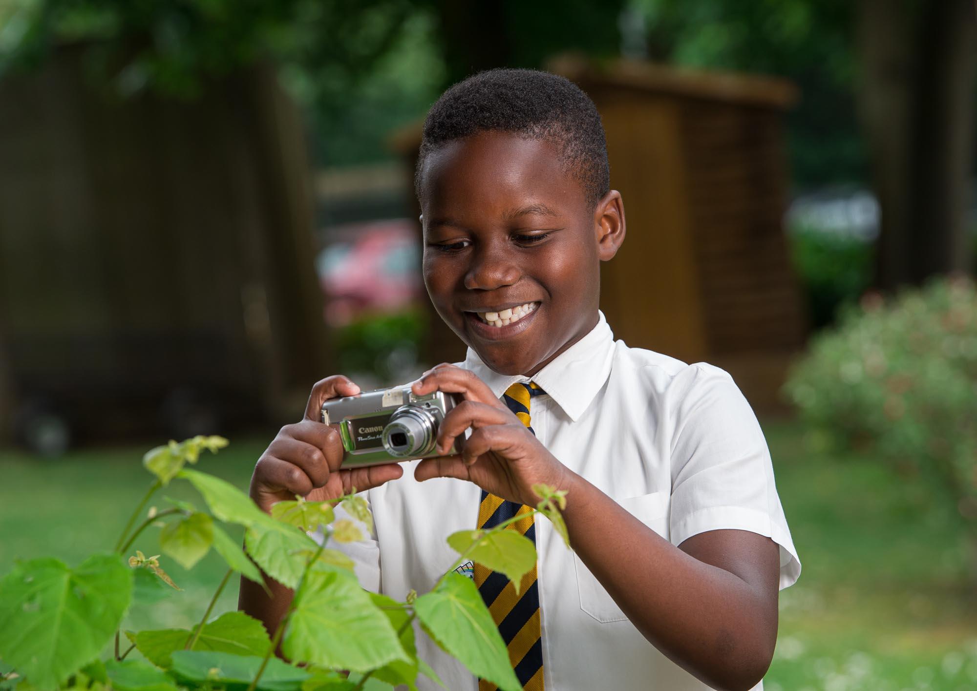 Boy taking photographs of plants