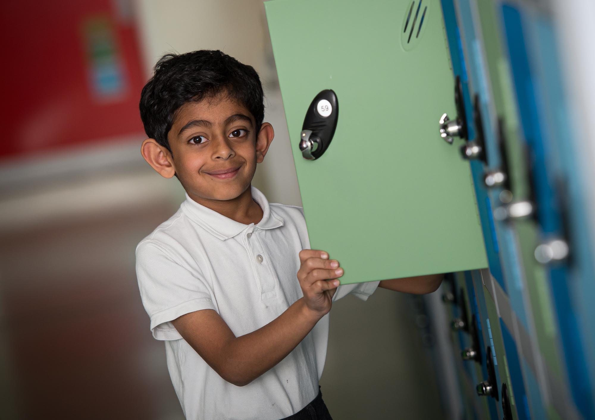 Boy opening locker in corridor