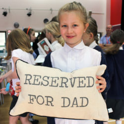 """Girl holding cushion with """"Reserved for dad"""" print"""