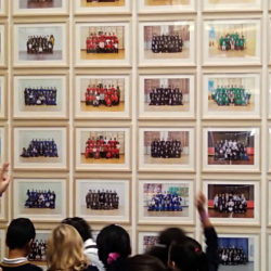 Children pointing at photos of school classes