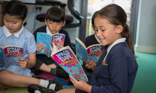Group of pupils on the floor reading George's Marvellous Medicine by Roald Dahl