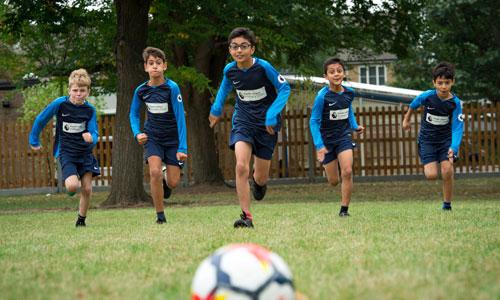 Boys' football team running towards football