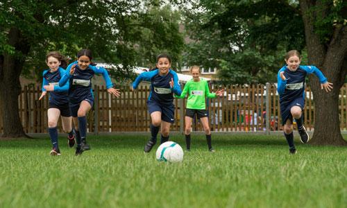 Girls' football team running towards football