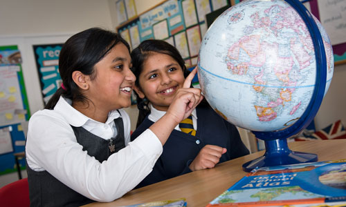 Two girls pointing at globe
