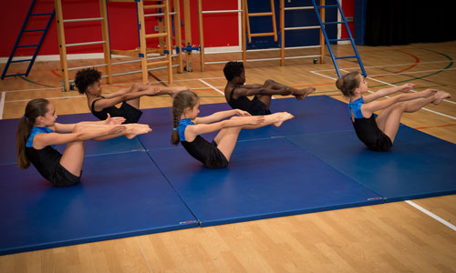 Five children on the mat doing gym squad