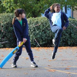 Girl jumping and throwing ball
